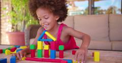 Happy little Afro girl playing with colorful building blocks Stock Footage