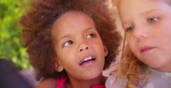 Afro girl and blonde friend focused on something Stock Footage