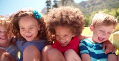 Mixed racial group of kid friends sitting together Stock Footage