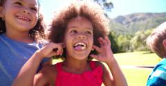 Little Afro girl with friends smiling in summer sunlight - stock footage