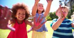 Little Afro girl showing hands full of blue paint Stock Footage