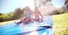 Littel girls sliding down a water slide happily Stock Footage