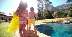 Children running with lilo towards swimming pool Stock Footage