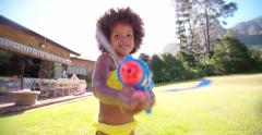 Afro girl splashing water at camera with squirt gun in slow motion Stock Footage
