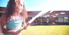 Little mixed race girl drinking water from a garden hose Stock Footage