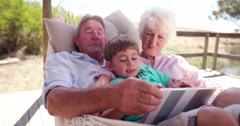 Grandparents and their grandson using a digital tablet Stock Footage