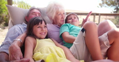 Grandparents spending time with their grandchildren in hammock Stock Footage