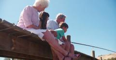 Grandparents sitting with their grandchildren on a jetty - stock footage