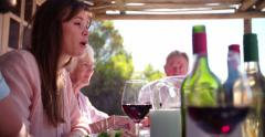 Three generation family enjoying a meal together outdoors - stock footage