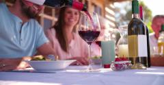 Man pouring wine while enjoying a family meal Stock Footage