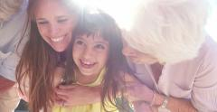 Laughing little girl with her mother and grandmother Stock Footage