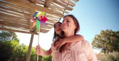 Mother and daughter outside with a colorful windmill - stock footage