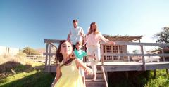 Couple holding hands while their children run on a jetty Stock Footage