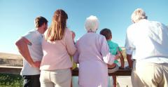 Rearview of a three generation family on a wooden jetty - stock footage