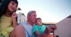 Grandpa reading a story to his grandkids outdoors Stock Footage