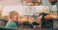 Children petending to drive an old vehicle on summer vacation Stock Footage