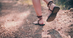 Girl walking with sandals in forest Stock Footage