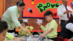 FULL SHOT. Children doing school activities, mistress help them. Stock Footage