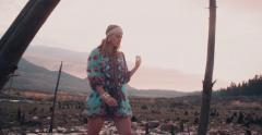 Girl in floral boho fashion in a desolate landscape - stock footage