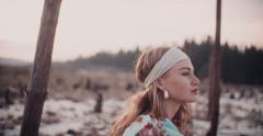Boho girl in a headband sitting in nature - stock footage