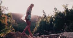 Boho girl in vintage dress stepping over stones at lake Stock Footage