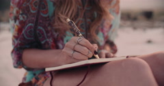 Boho girl writing in her diary wearing a floral dress - stock footage