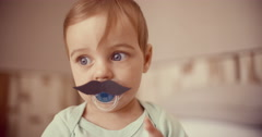 Baby boy touching a mustache that's stuck onto his pacifier Stock Footage