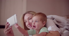 Mother and baby son with smart phone in bed Stock Footage