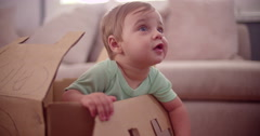 Baby boy playing in a cardboard box - stock footage