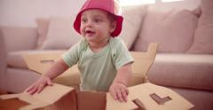 Excited baby wearing a plastic bowl as a hat Stock Footage