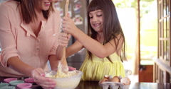 Girl helping her mom by stirring the ingredients for cake - stock footage