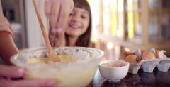 Girl helping her mom in the kitchen to bake a cake - stock footage