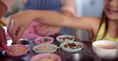 Mom and daughter decorating cupcakes together Stock Footage