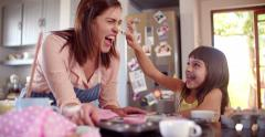 Mom and daughter having fun together in kitchen while baking - stock footage