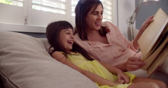 Little girl laughing while reading a book with her mom - stock footage