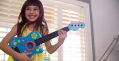 Little girl playing a guitar in the lounge Stock Footage