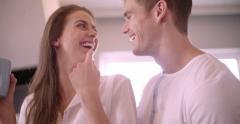 Guy lovingly kissing his girlfriend in their kitchen - stock footage