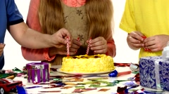 Children's hands turn put their candles in the cake, dressed bright things Stock Footage