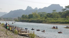 Tourists relax at the river while canoes pass,Vang Vieng,Laos Stock Footage
