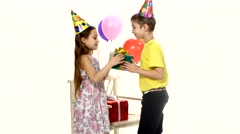 Children give gifts to birthday girl at a time. Girl accepts hugs Stock Footage