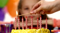 Hand ignites red candle on yellow cake, girl in the back. Rasfokus Stock Footage