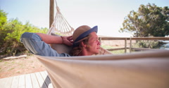 Teen guy wearing a hat while resting in a hammock - stock footage