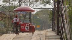 A ice cream seller drives over a wooden bridge,Vang Vieng,Laos Stock Footage