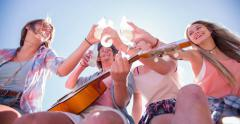 Friends saying cheers with alcopops outdoors with sun flare Stock Footage