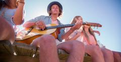 Friends laughing together with alcopops and a guitar on holiday Stock Footage