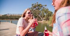 Teen girls laughing on a jetty on a summer break Stock Footage