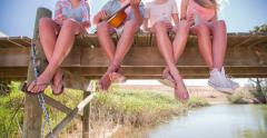 Teen friend's legs and feet sitting on lake jetty Stock Footage