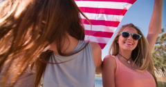 Cool teen friends smiling and holding an American flag - stock footage