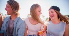 Teens eating pizza outdoors with sun flare Stock Footage