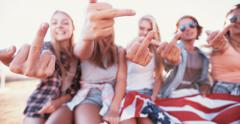 Rebellious teens showing their middle fingers and holding American flag Stock Footage